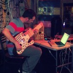 Some kind of synth guitar made from a giant popsicle stick